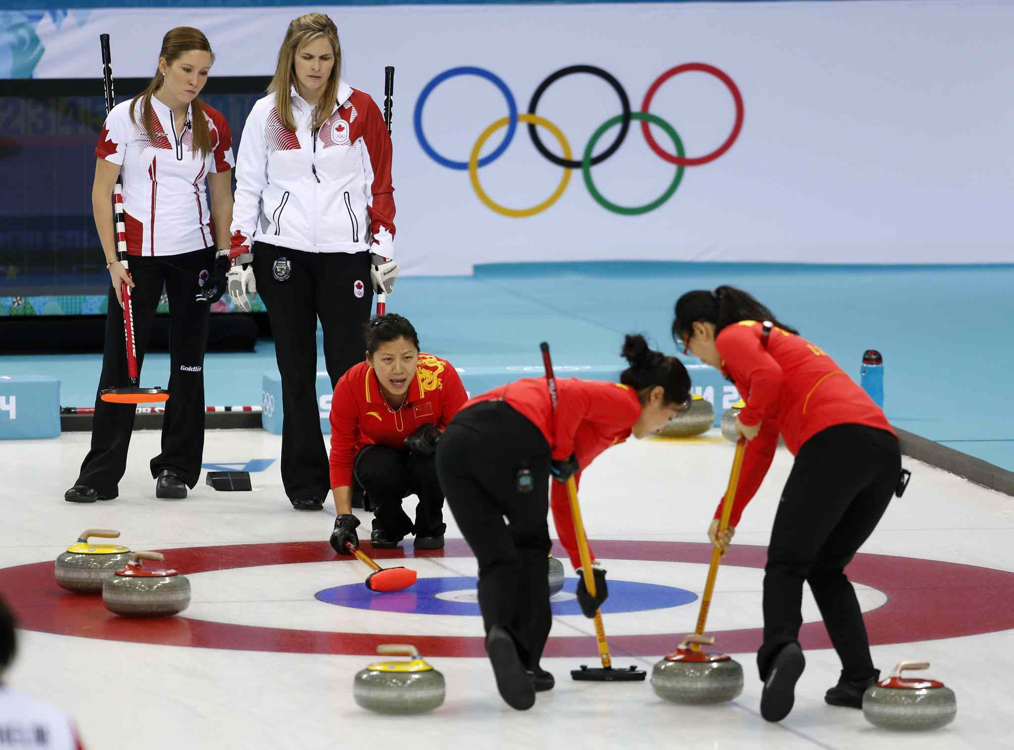 China's Liu Yin shouts instructions to her sweepers as Canada's Kaitlyn Lawes (left) and skip Jennifer Jones look on.