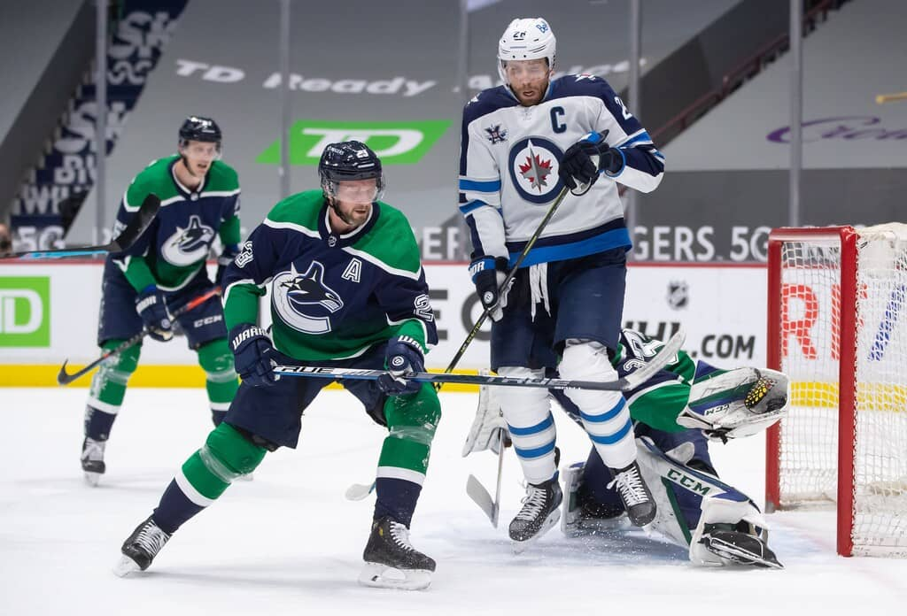 Vancouver Canucks goalie Thatcher Demko, back right, makes a glove save while being screened by Winnipeg Jets' Blake Wheeler during the first period Friday. THE CANADIAN PRESS/Darryl Dyck
