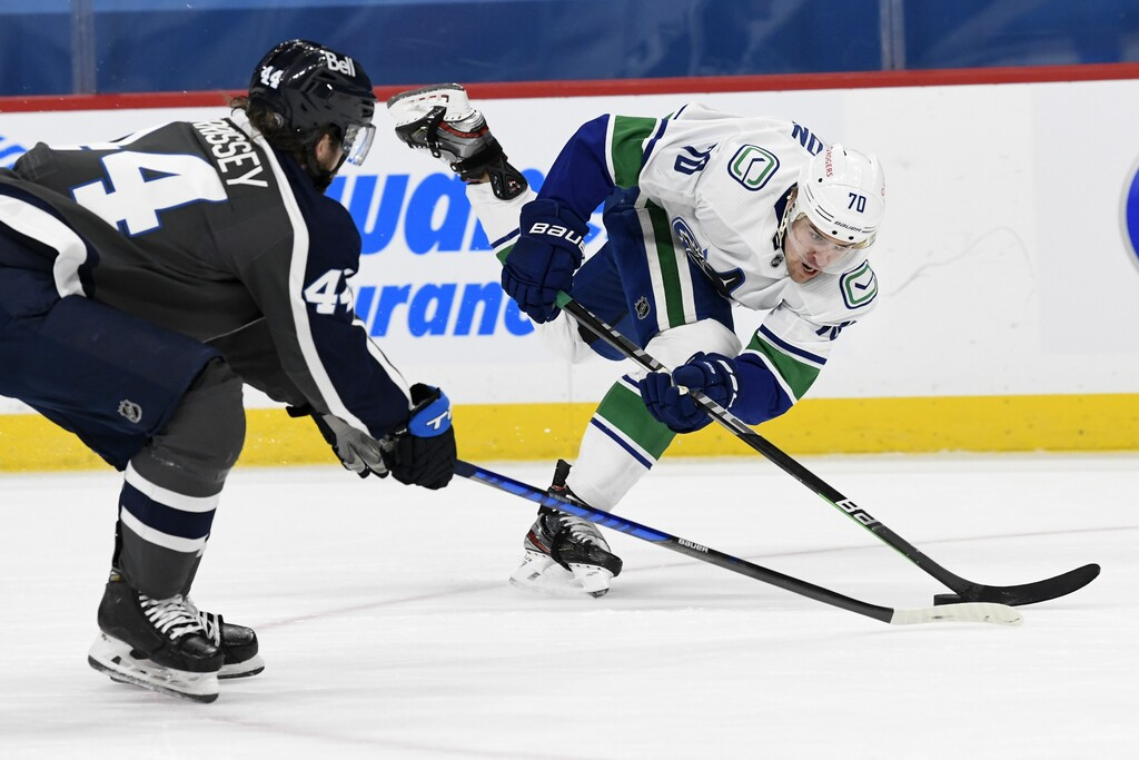Vancouver Canucks' Tanner Pearson tries to keep control of the puck while Winnipeg Jets' Josh Morrissey defends during the first period. THE CANADIAN PRESS/Fred Greenslade