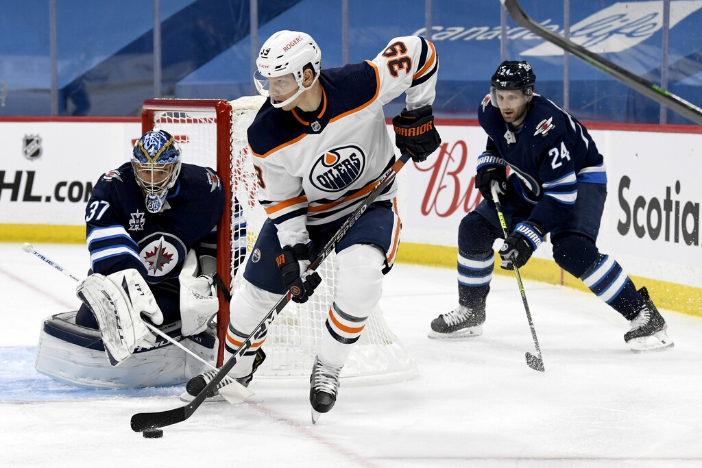 Edmonton Oilers' Alex Chiasson looks to pass the puck in front of Winnipeg Jets goaltender Connor Hellebuyck and Derek Forbort during the first period.
