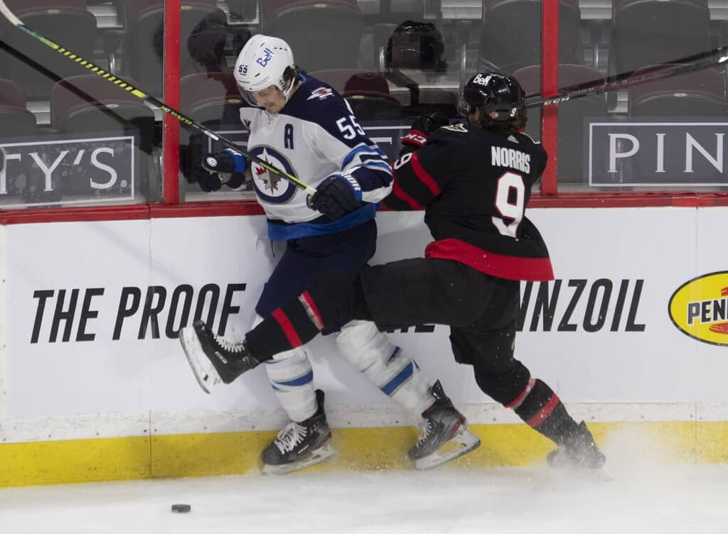 Winnipeg Jets' Mark Scheifele collides with Ottawa Senators' Josh Norris along the boards during the second period. THE CANADIAN PRESS/Adrian Wyld
