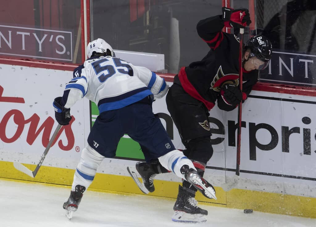 Ottawa Senators left wing Brady Tkachuk gets the puck under control after colliding with Winnipeg Jets centre Mark Scheifele along the boards during the first period. THE CANADIAN PRESS/Adrian Wyld
