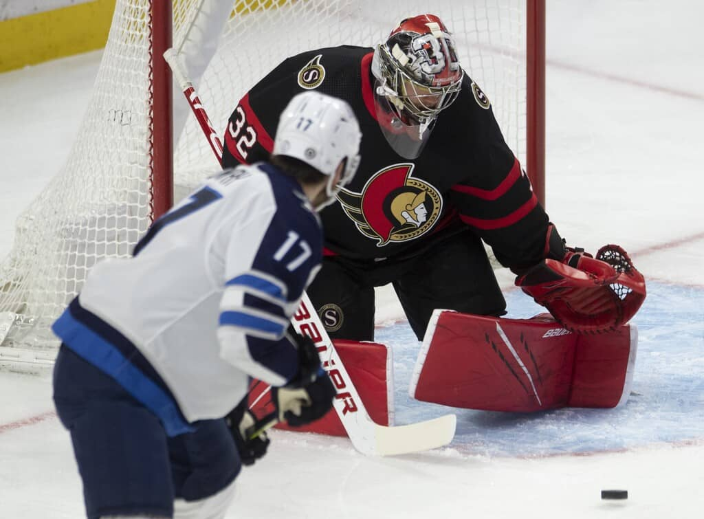 Winnipeg Jets centre Adam Lowry pressures Ottawa Senators goaltender Filip Gustavsson during the first period. THE CANADIAN PRESS/Adrian Wyld