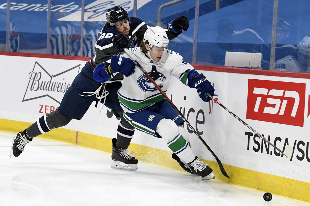 Winnipeg Jets' Nathan Beaulieu checks Vancouver Canucks' Adam Gaudette during the first period. THE CANADIAN PRESS/Fred Greenslade