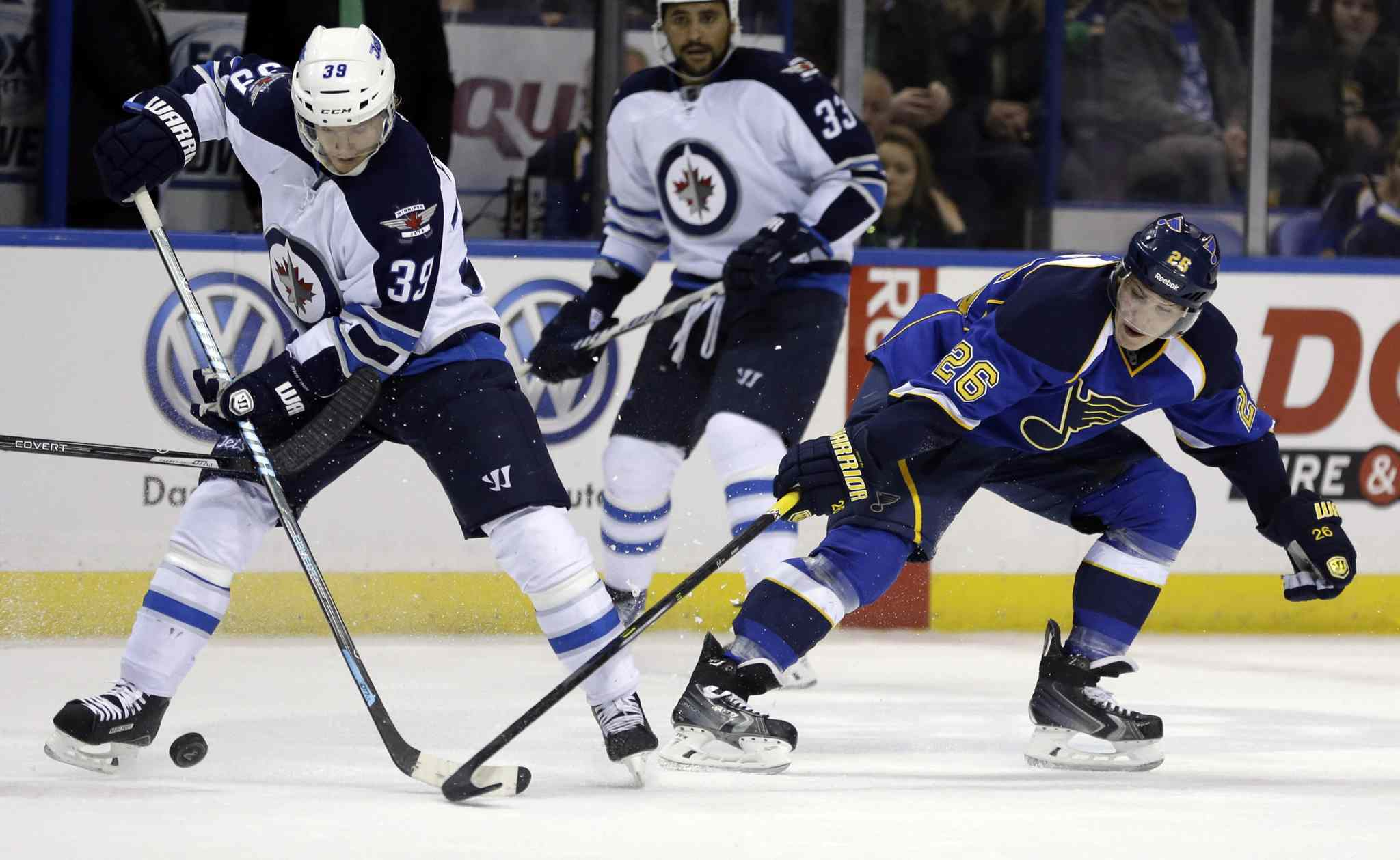 Jets defenceman Tobias Enstrom controls the puck as the Blues' Dmitrij Jaskin defends during the second period.