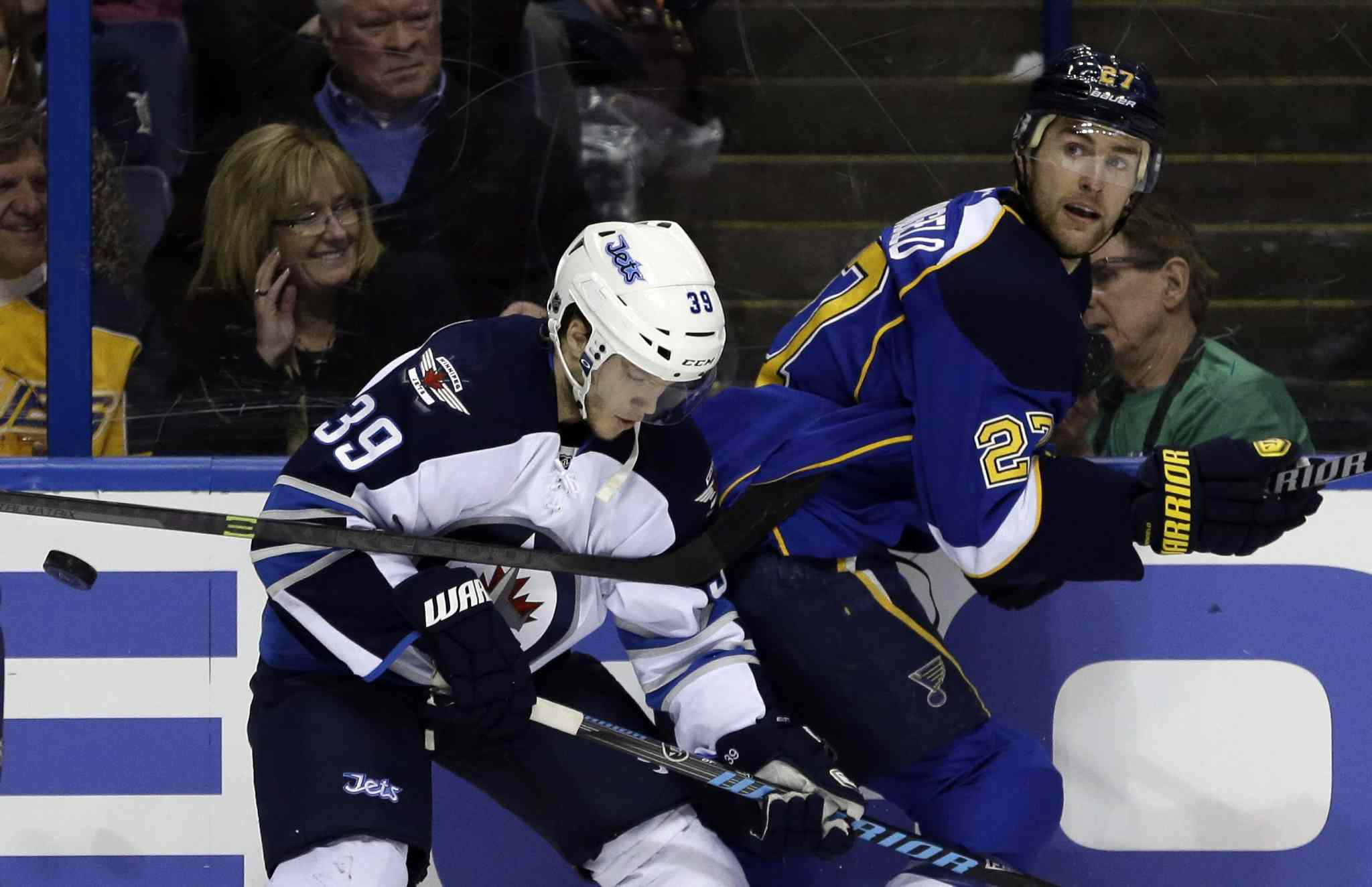 Jets defenceman Tobias Enstrom and Blues defenceman Alex Pietrangelo chase after a loose puck in the second period.
