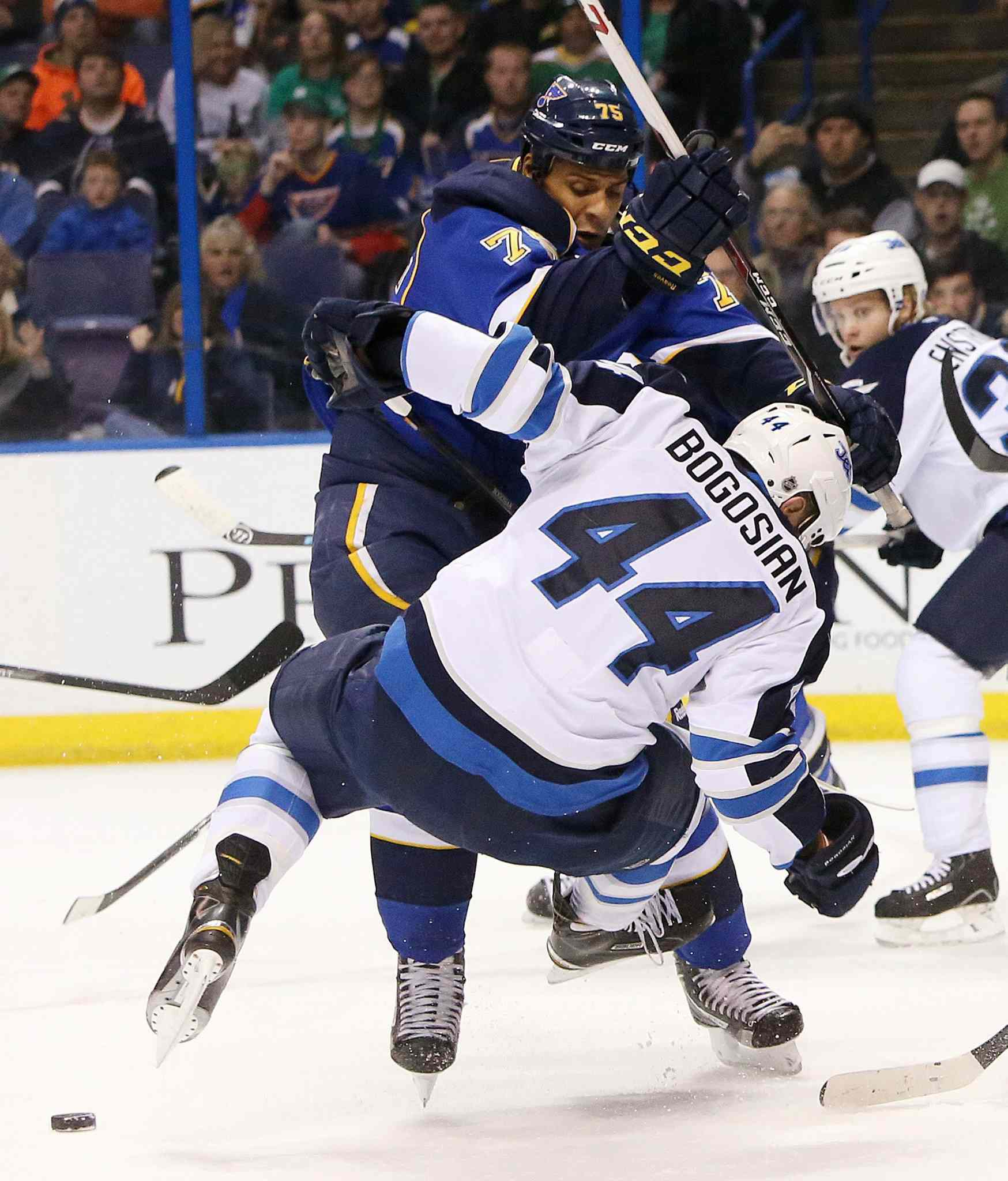 Blues forward Ryan Reaves knocks down Jets defenceman Zach Bogosian in the first period.