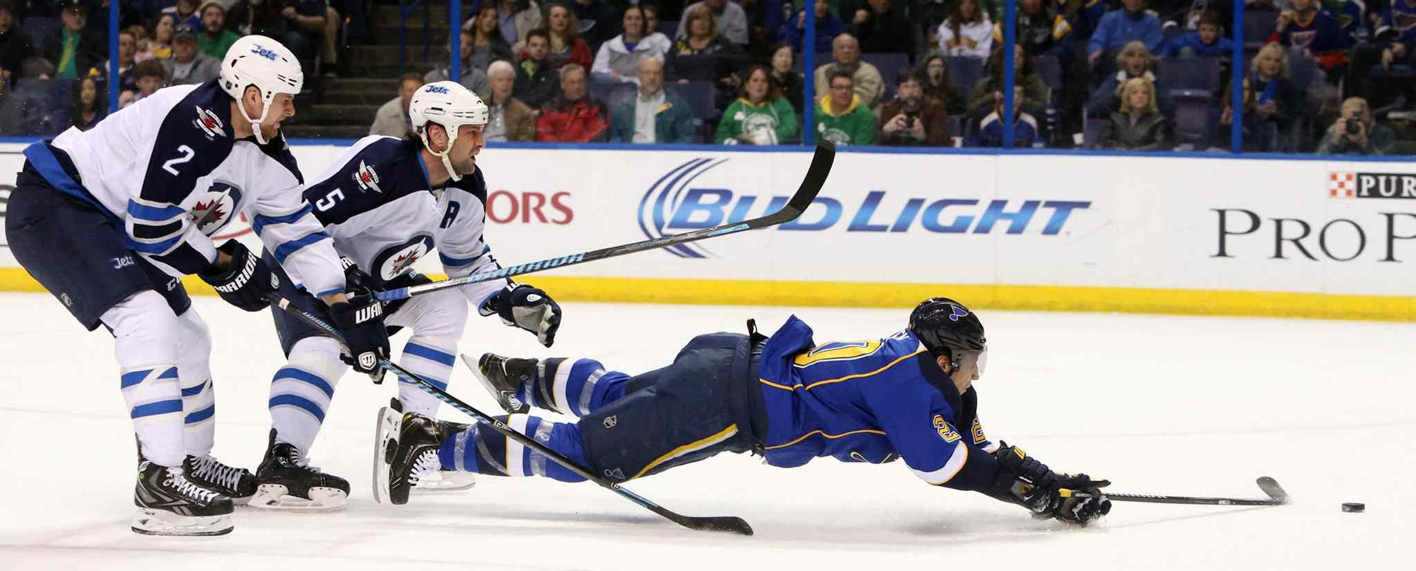 Blues left-winger Alexander Steen is knocked down from behind by Jets defenceman Mark Stuart (5) as he rushes the net in first-period action.