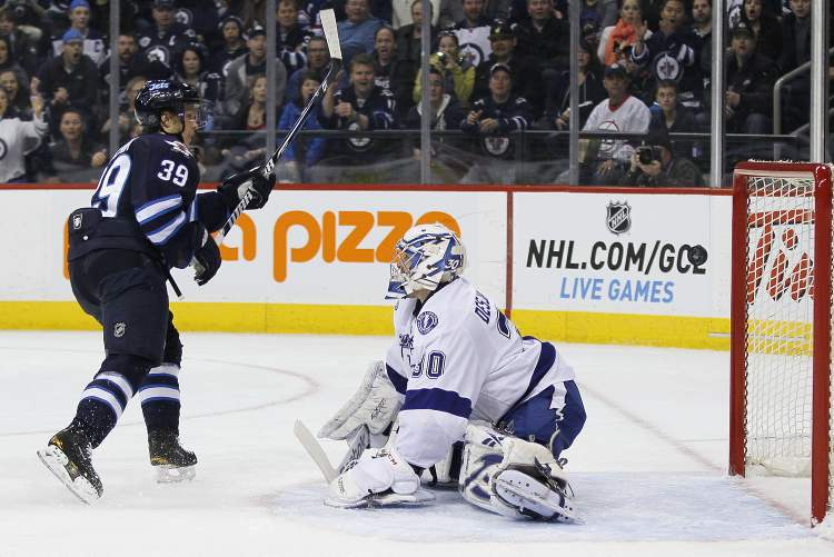 Winnipeg Jets defenceman Tobias Enstrom scores on Tampa Bay Lightning goaltender Cedrick Desjardins during second-period NHL action in Winnipeg on Sunday. The goal proved to be the game-winner. (JOHN WOODS / WINNIPEG FREE PRESS)