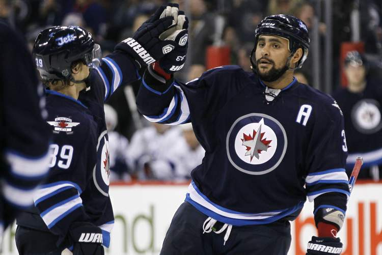 Winnipeg Jets defencemen Dustin Byfuglien (right) and Tobias Enstrom celebrate Byfuglien's goal against the Tampa Bay Lightning during second-period NHL action in Winnipeg on Sunday. (JOHN WOODS / WINNIPEG FREE PRESS)
