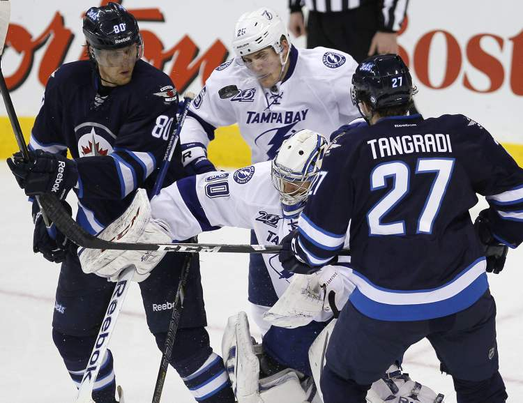 Winnipeg Jets' Nik Antropov (80) and Eric Tangradi and Tampa Bay Lightning's Matthew Carle look for the rebound off of Lightning goaltender Cedrick Desjardins during third-period NHL action in Winnipeg on Sunday.