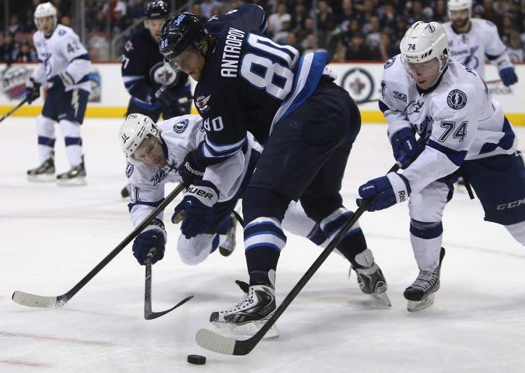 Winnipeg Jets' Nik Antropov battles for the puck between Tampa Bay Lightnings' Tom Pyatt (left) and Ondrej Palat during the second period pf an NHL game in Winnipeg, Sunday. (Trevor Hagan / THE CANADIAN PRESS)