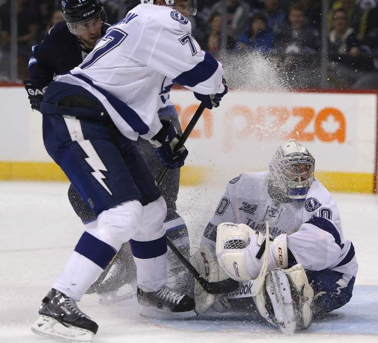 Tampa Bay Lightning goaltender Cedrick Desjardins gets a face full of snow as Winnipeg Jets' Andrew Ladd and Lightnings' Victor Hedman  crash the net during the second in Winnipeg, Sunday. (Trevor Hagan / THE CANADIAN PRESS)