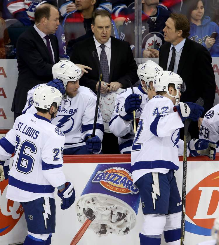 Tampa Bay Lightning assistant coaches Daniel Lacroix and Martin Raymond and player development coach Steve Thomas in place of fired head coach, Guy Boucher, during first-period NHL action against the Winnipeg Jets' in Winnipeg, Sunday.  (Trevor Hagan / THE CANADIAN PRESS)