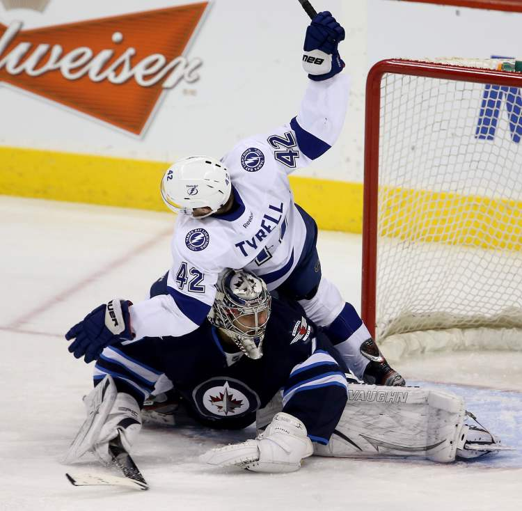 Tampa Bay Lightnings' Dana Tyrell crashes into Winnipeg Jets goaltender Ondrej Pavelec during the first period in Winnipeg, Sunday. (Trevor Hagan / THE CANADIAN PRESS)