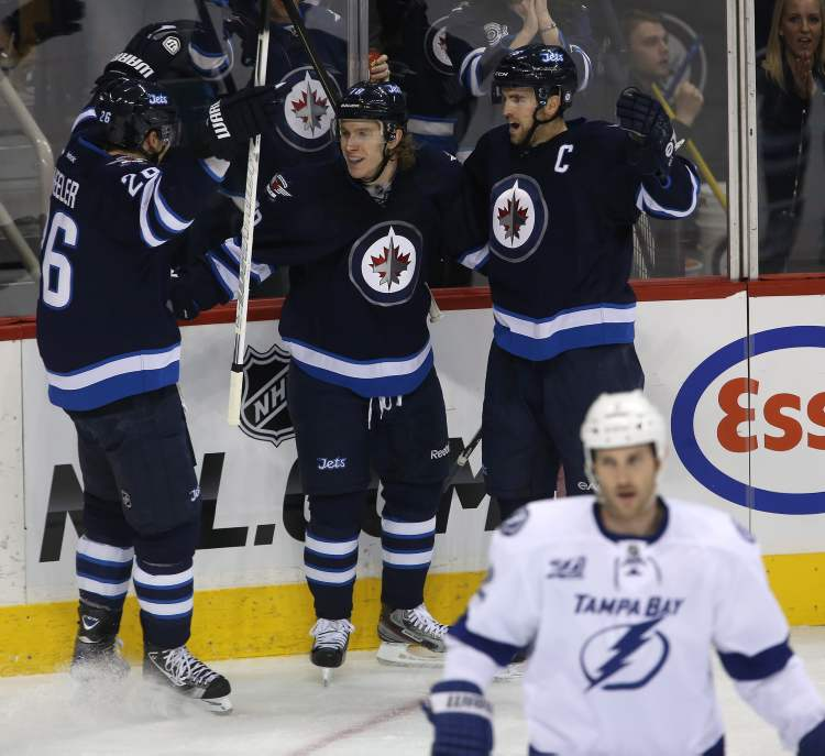Winnipeg Jets Blake Wheeler, Bryan Little and Andrew Ladd (from left) celebrate after Little opened the scoring against the Tampa Bay Lightning during first-period NHL action in Winnipeg, Sunday.  (Trevor Hagan / THE CANADIAN PRESS)