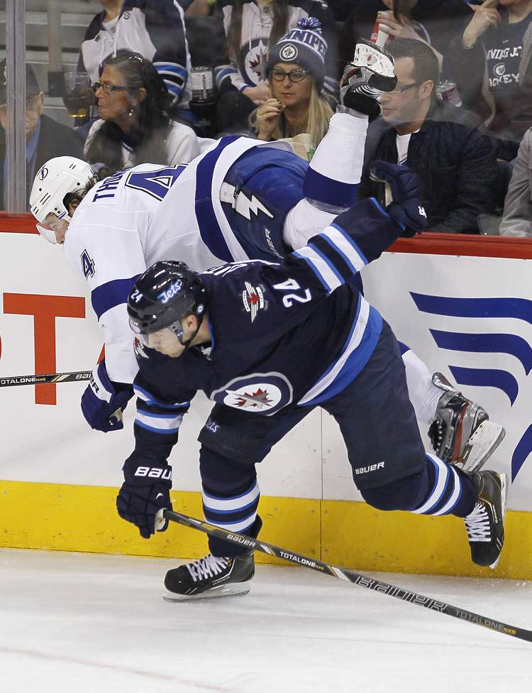 Winnipeg Jets' Grant Clitsome (24) checks Tampa Bay Lightning's Nate Thompson during first-period NHL action in Winnipeg on Sunday. (JOHN WOODS / WINNIPEG FREE PRESS)