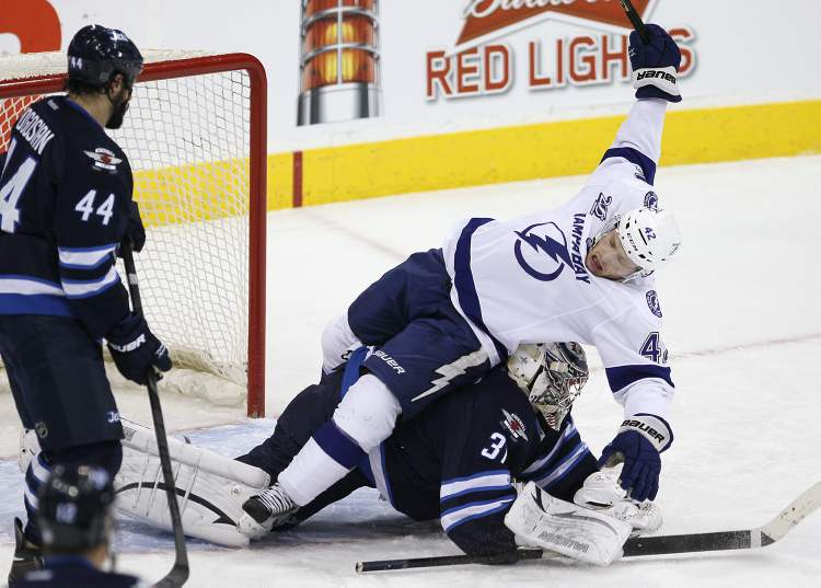 Tampa Bay Lightning's Dana Tyrell goes over the top of Winnipeg Jets goaltender Ondrej Pavelec as Jets defenceman Zach Bogosian looks on during an NHL game in Winnipeg on Sunday.