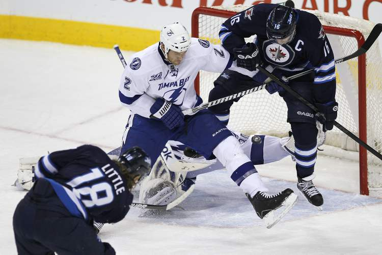 Winnipeg Jets' Bryan Little scores through the legs of Jets' Andrew Ladd on Tampa Bay Lightning goaltender Cedrick Desjardins and defenceman Eric Brewer during first-period NHL action in Winnipeg on Sunday. (JOHN WOODS / WINNIPEG FREE PRESS)