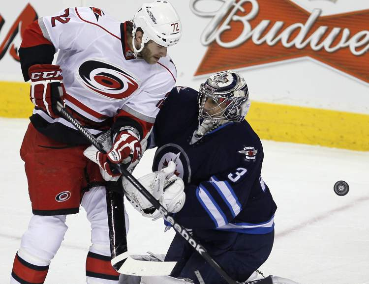 Carolina Hurricanes' Nicolas Blanchard (72) can't knock this loose puck past Winnipeg Jets goaltender Ondrej Pavelec during the first period. (JOHN WOODS / THE CANADIAN PRESS)
