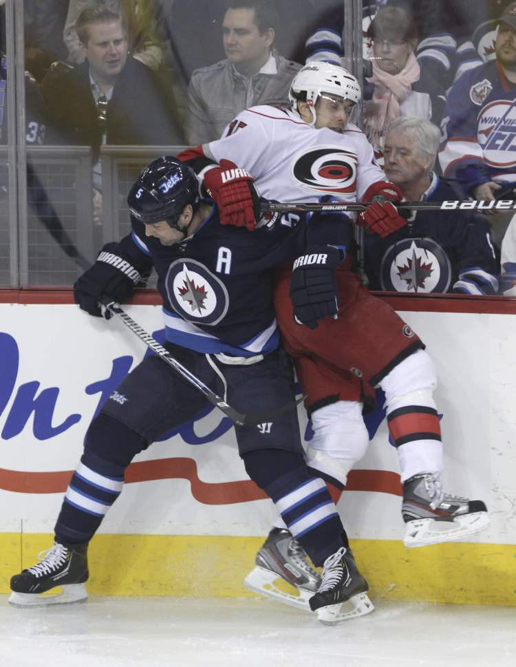 Winnipeg Jets' Mark Stuart pins Carolina Hurricanes' Tuomo Ruutu to the boards during an NHL game at the MTS Centre Thursday. (MIKE DEAL / WINNIPEG FREE PRESS)