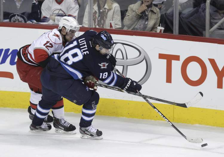 Winnipeg Jets' Bryan Little keeps control of the puck in the corner with Carolina Hurricanes' Eric Staal checking him.  (MIKE DEAL / WINNIPEG FREE PRESS)