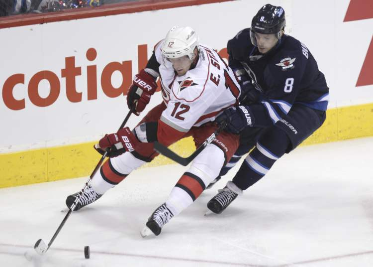 Winnipeg Jets' Alexander Burmistrov is hot on the heels of Carolina Hurricanes' Eric Staal in the first period.