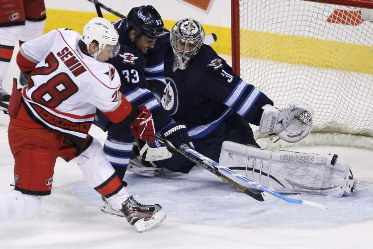 Carolina Hurricanes' Alexander Semin scores to send the game into overtime as Jets defenceman Dustin Byfuglien tries to defend. (JOHN WOODS / THE CANADIAN PRESS)