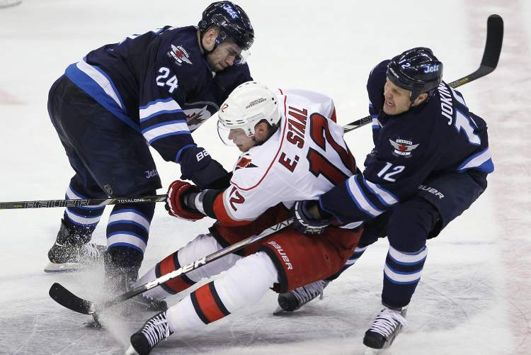 Winnipeg Jets' Grant Clitsome (24) and Olli Jokinen (12) double-team Carolina Hurricanes' Eric Staal during the second period. (JOHN WOODS / THE CANADIAN PRESS)