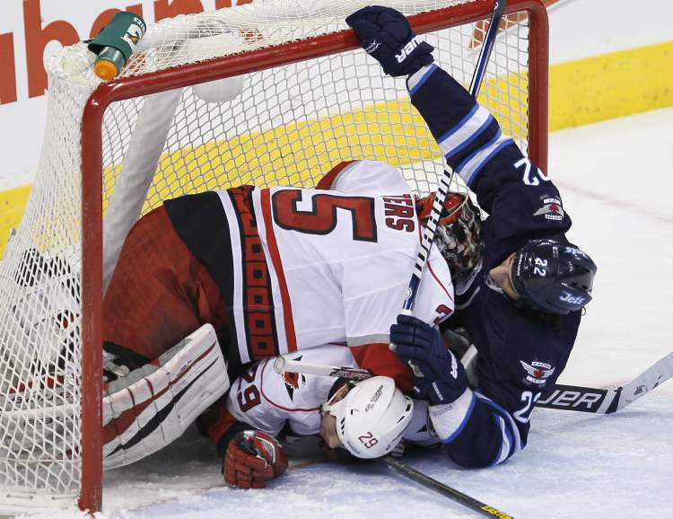 Winnipeg Jets' Chris Thorburn crashes into Carolina Hurricanes player Tim Wallace and goaltender Justin Peters.