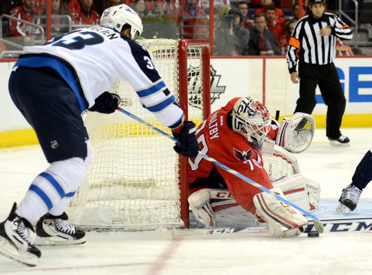 Winnipeg Jets defenceman Dustin Byfuglien attempts to tuck the puck past Washington Capitals goalie Braden Holtby in the first period at the Verizon Center in Washington, D.C., Tuesday. (Chuck Myers / Tribune Media/MCT)