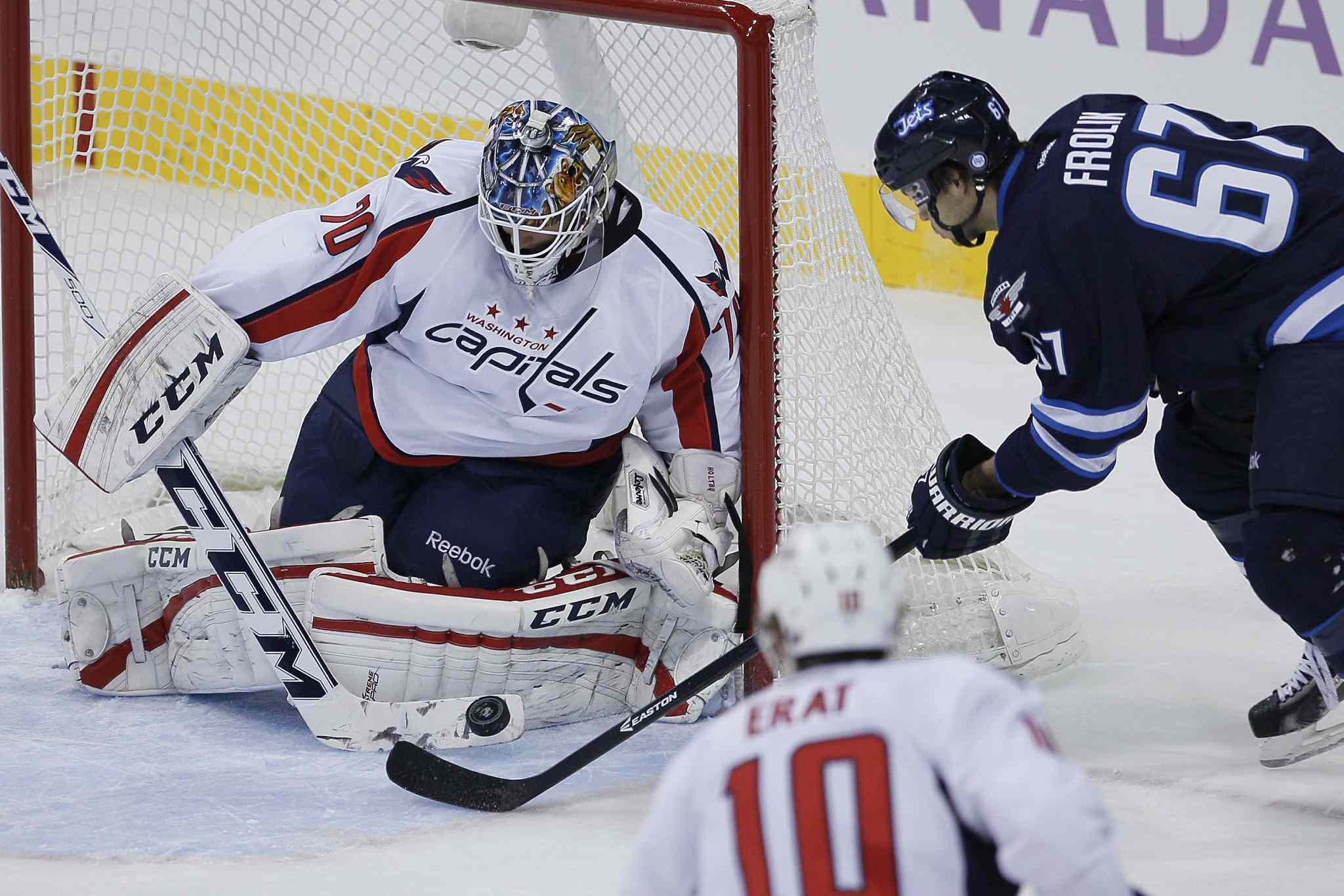 Washington Capitals goaltender Braden Holtby makes a save on a close-in scoring chance by Winnipeg Jets forward Michael Frolik during first-period NHL action at the MTS Centre in Winnipeg Tuesday.