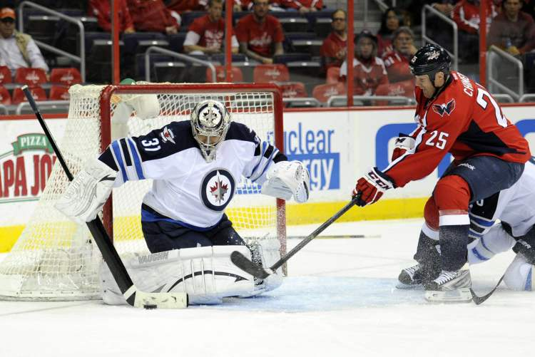 Winnipeg Jets goalie Ondrej Pavelec tracks the puck against Washington Capitals left-winger Jason Chimera during the first period. (Nick Wass / the associated press)