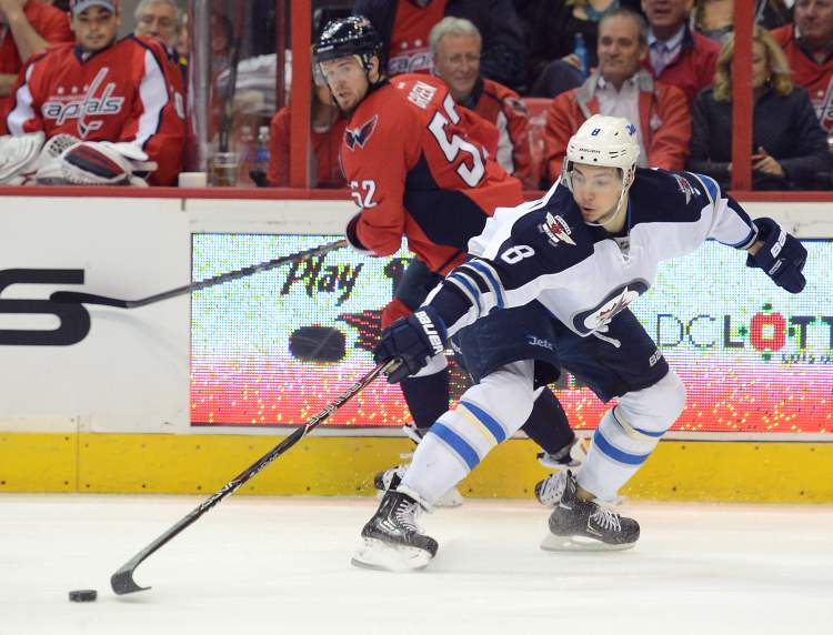 Winnipeg Jets centre Alex Burmistrov pushes the puck forward with one hand as Washington Capitals defenceman Mike Green looks on in the second period.
