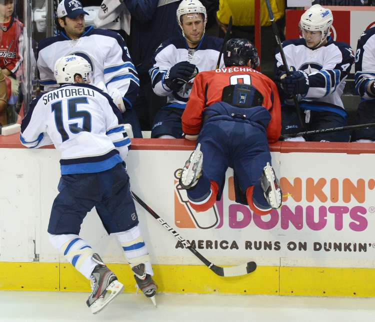 Washington Capitals left-winger Alex Ovechkin tumbles into the Winnipeg Jets bench after a push by Winnipeg Jets centre Mike Santorelli in the third period.
