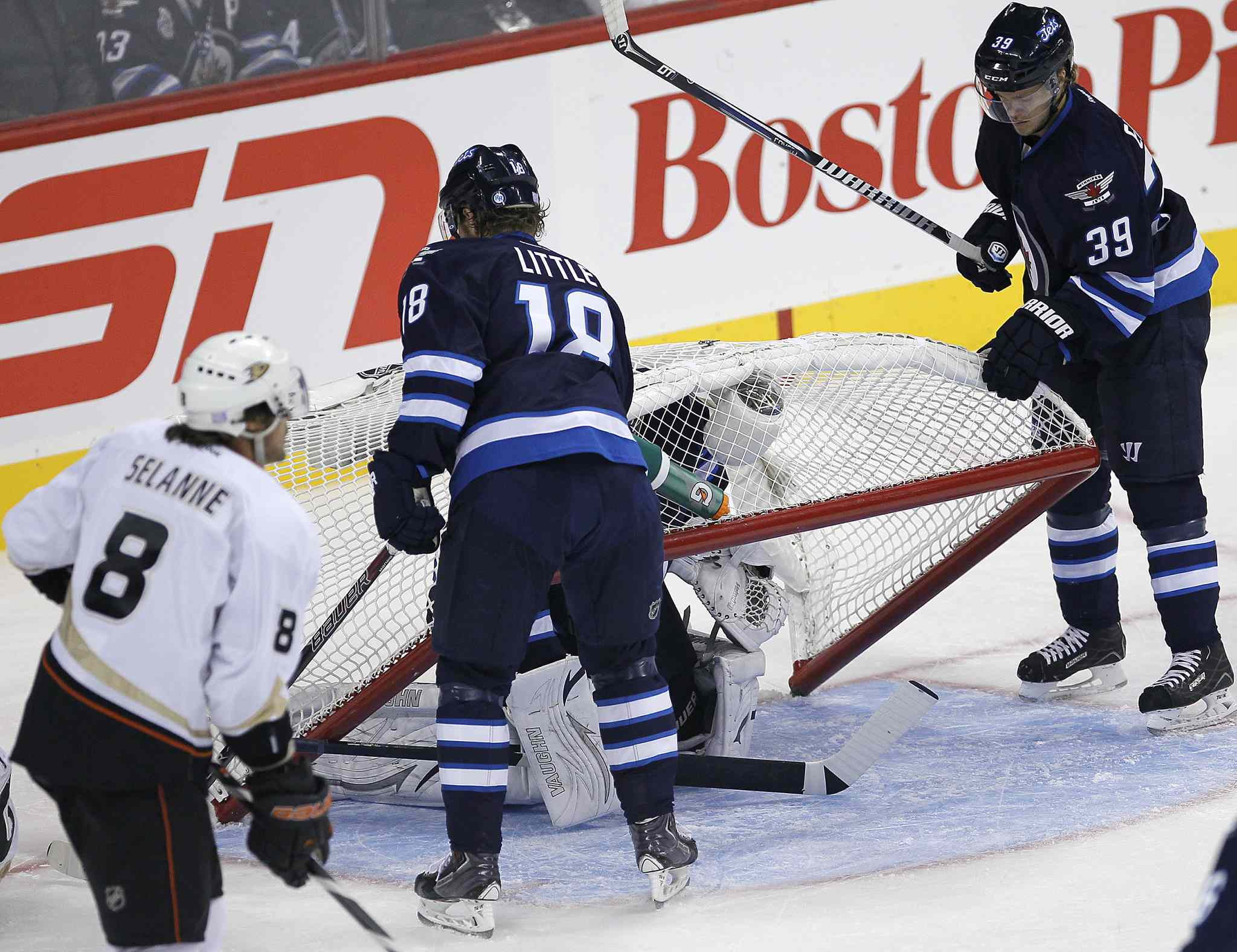 Winnipeg Jets' Bryan Little (18) and Toby Enstrom lift the net off goaltender Ondrej Pavelec in the first period as the Ducks' Teemu Selanne cruises past.