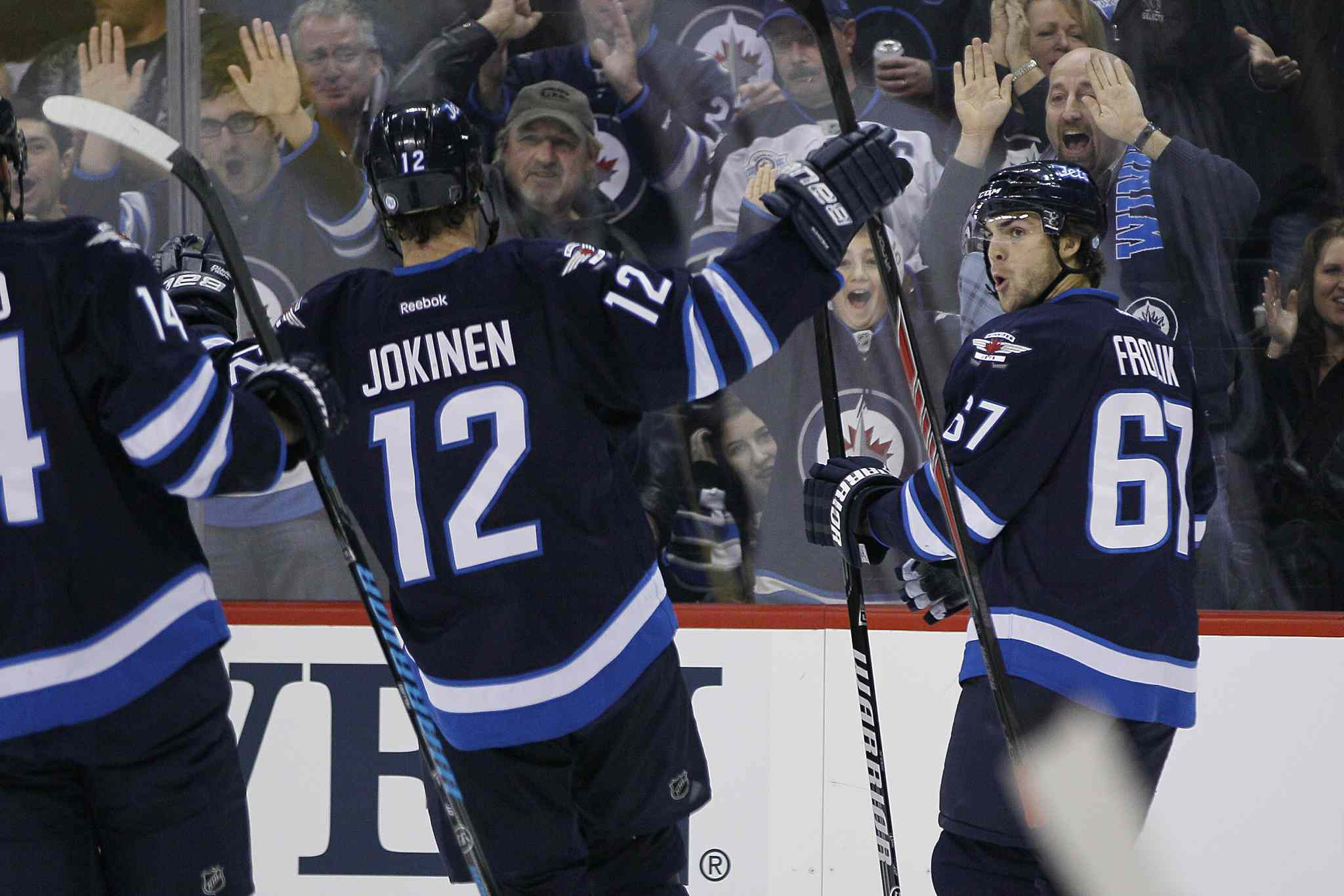 Winnipeg Jets' Michael Frolik (67), Olli Jokinen (12) and Anthony Peluso (14) celebrate Frolik's goal against the Calgary Flames during second period NHL action in Winnipeg on Monday, November 18, 2013.