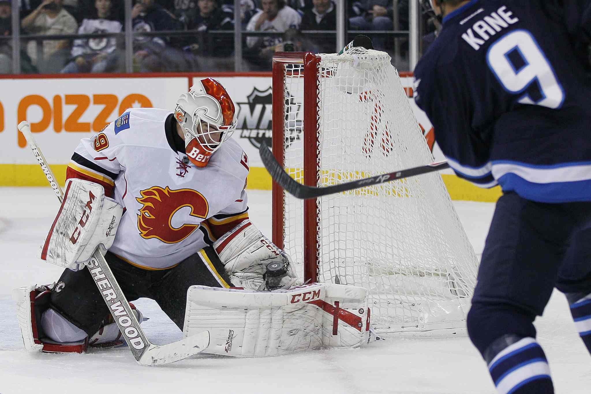 Winnipeg Jets' Evander Kane (9) gets stopped by Calgary Flames' goaltender Reto Berra (29) during second period NHL action in Winnipeg on Monday, Nov. 18, 2013.