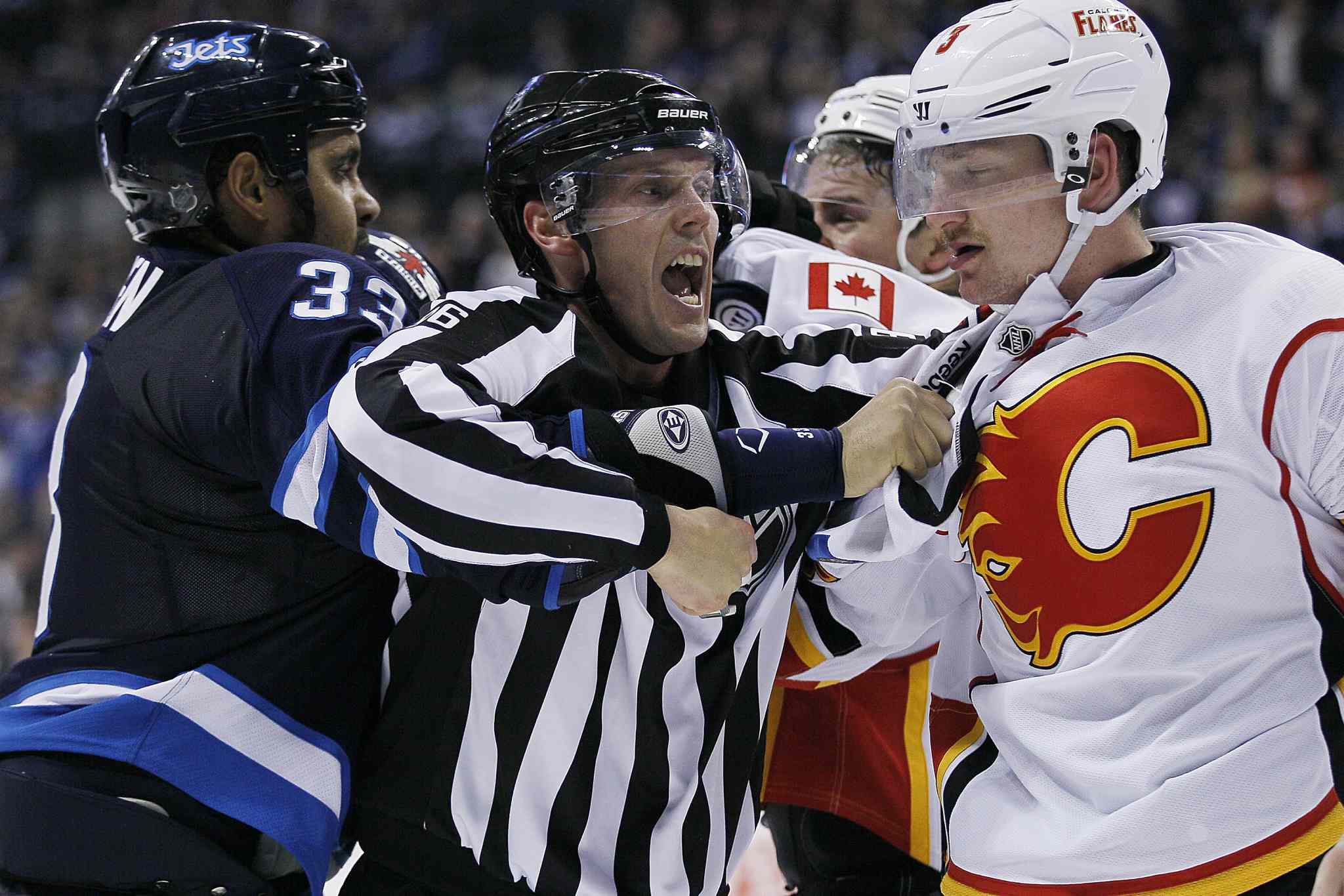 A linesman attempts to split up Winnipeg Jets' Dustin Byfuglien (33) and Calgary Flames' Ladislav Smid (3) and Chris Butler (44) after the second period buzzer goes during NHL action in Winnipeg on Monday, Nov. 18, 2013.