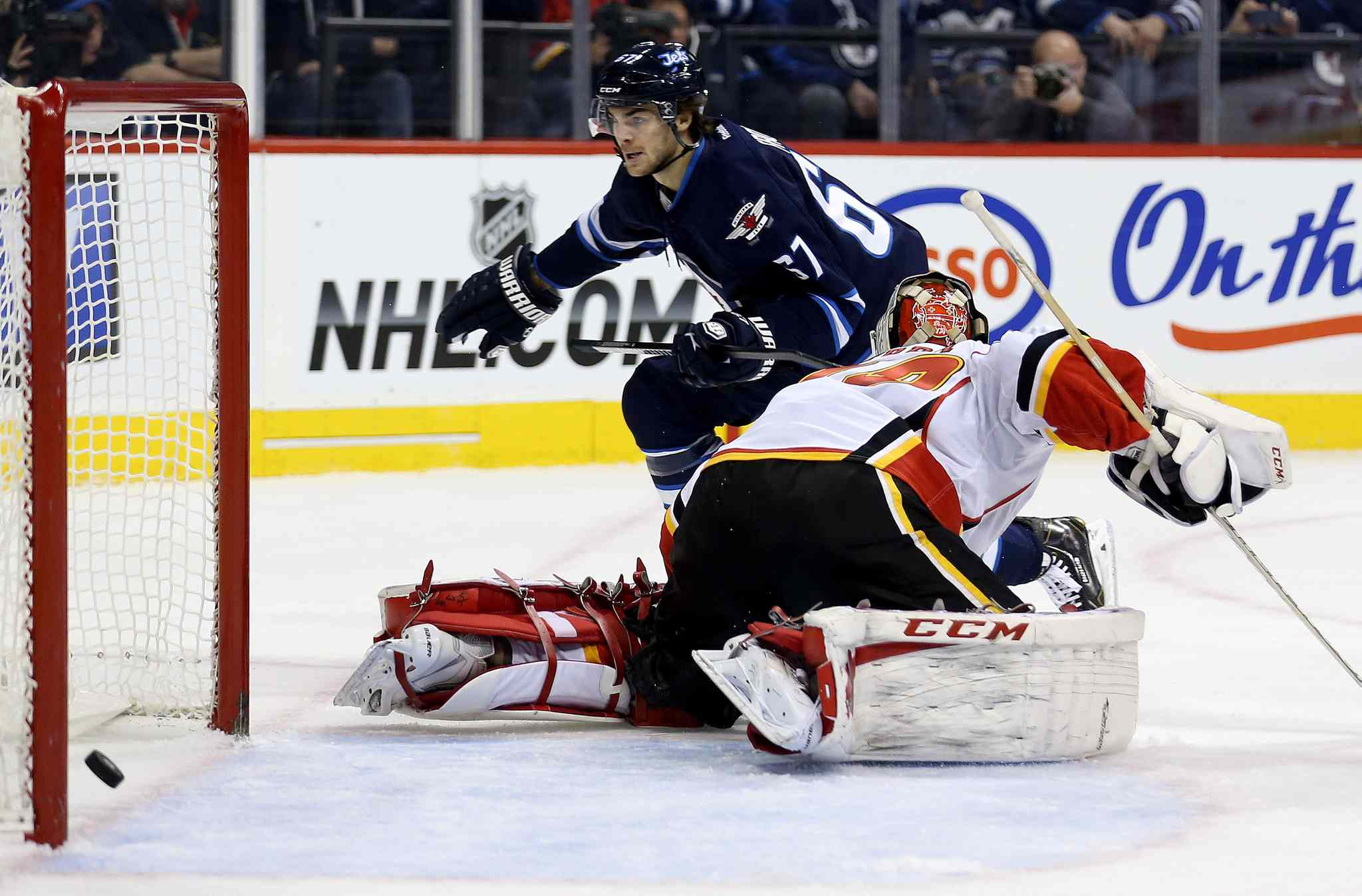 Winnipeg Jets' Michael Frolik (67) scores on Calgary Flames' goaltender Reto Berra (29) during second period NHL hockey action in Winnipeg Monday, Nov. 18, 2013.