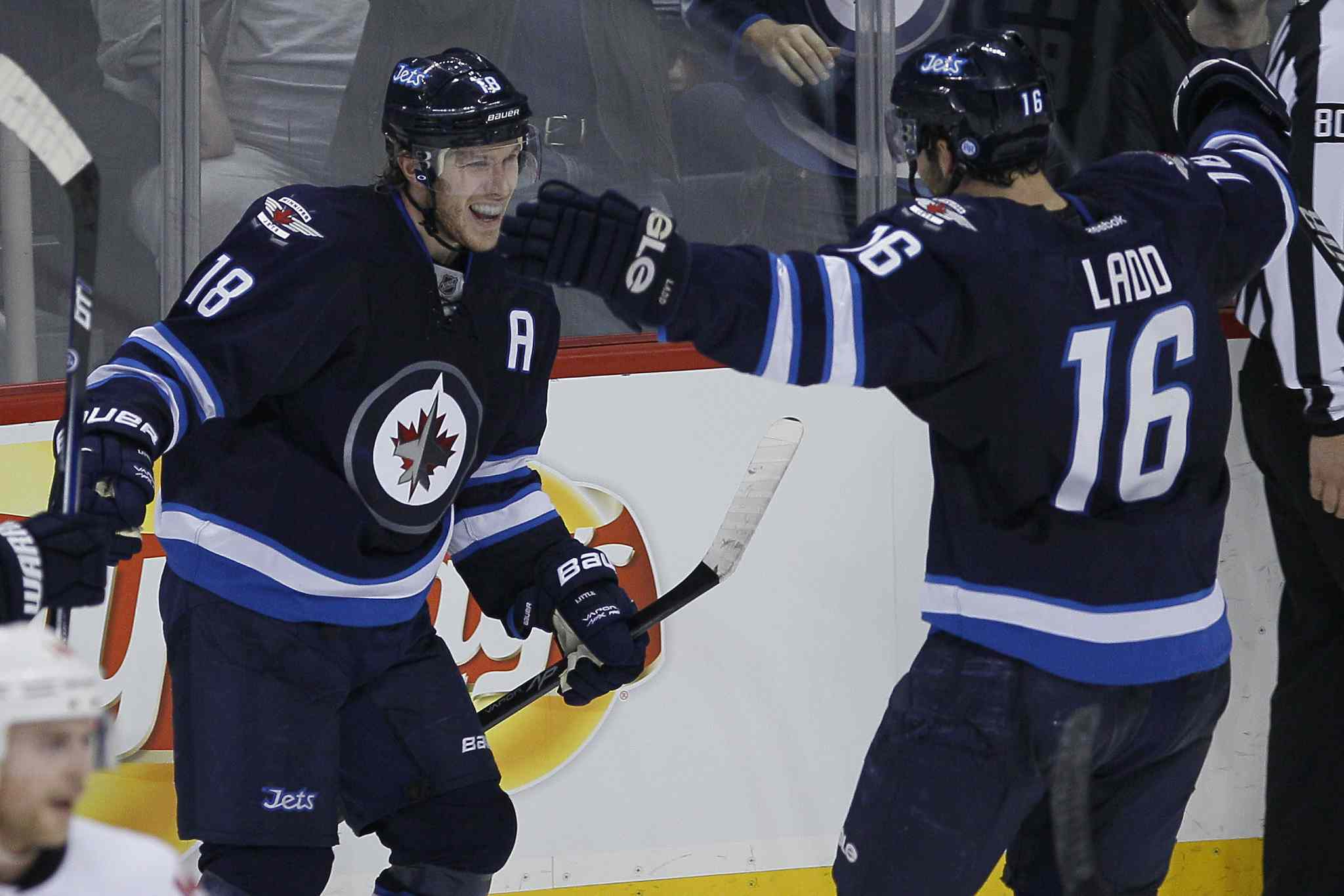 Winnipeg Jets' Bryan Little (18) and Andrew Ladd (16) celebrate  Little's goal against the Calgary Flames with 6 seconds left in the  during third period NHL action in Winnipeg on Monday, Nov. 18, 2013.