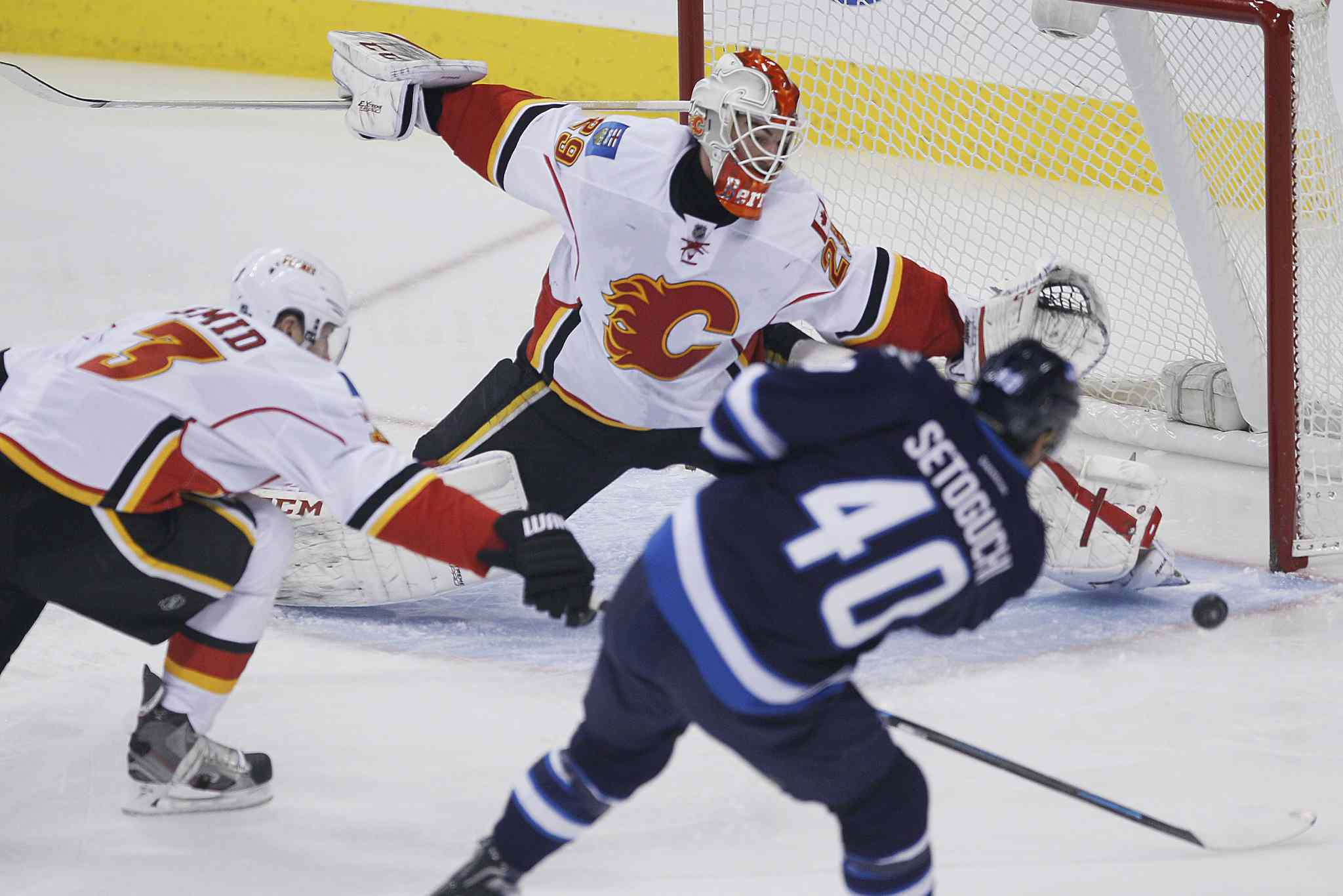 Calgary Flames' goaltender Reto Berra (29) gets his toe on the shot from Winnipeg Jets' Devin Setoguchi (40) as Flames' Ladislav Smid (3) attempts to knock the puck away during first period NHL action in Winnipeg on Monday, Nov. 18, 2013.