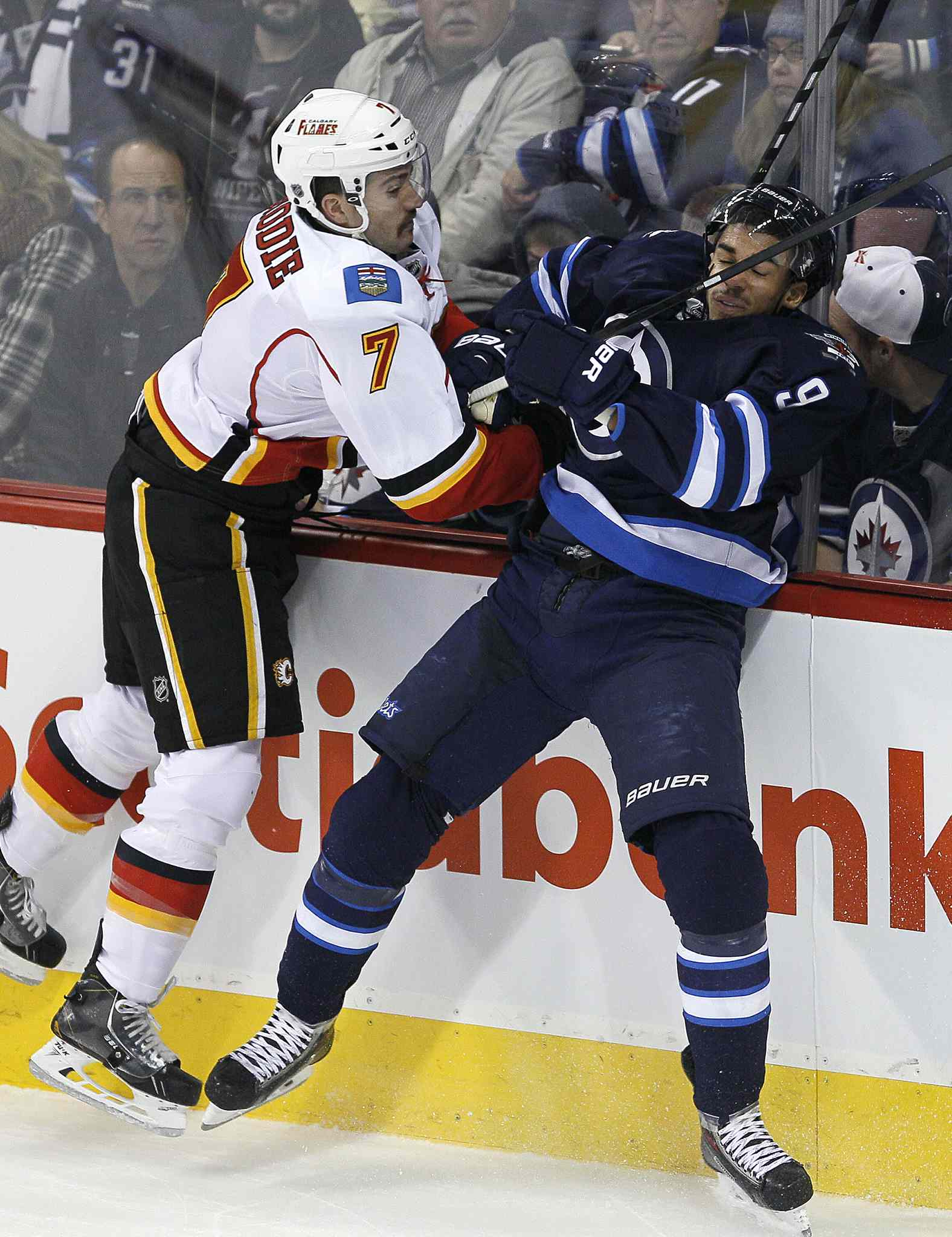Winnipeg Jets' Evander Kane (9) misses the check on Calgary Flames' TJ Brodie (7) during first period NHL action in Winnipeg on Monday, Nov. 18, 2013.