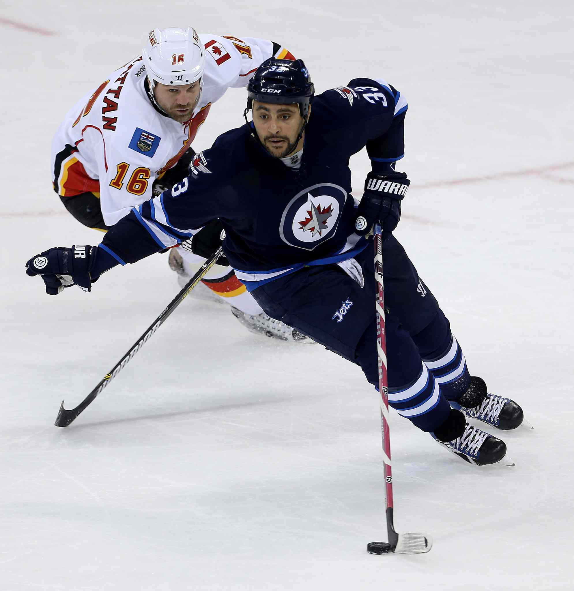 Calgary Flames' Brian McGrattan (16) and Winnipeg Jets' Dustin Byfuglien (33) fight for the puck during first period NHL hockey action in Winnipeg Monday, November 18, 2013.