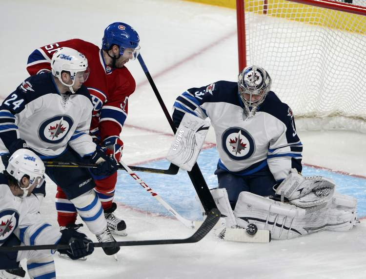Montreal Canadiens centre David Desharnais is stopped by Winnipeg Jets goalie Ondrej Pavelec and defenceman Grant Clitsome (24) during the second period of Thursday's game in Montreal.