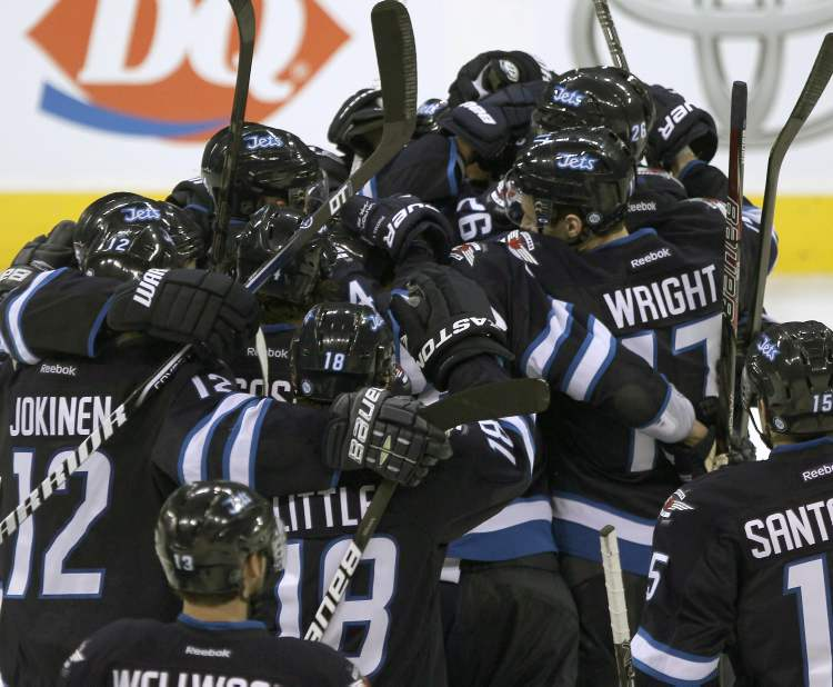 Winnipeg Jets players mob captain Andrew Ladd after his shootout goal sealed the deal against the Tampa Bay Lightning. (JOE BRYKSA / WINNIPEG FREE PRESS)