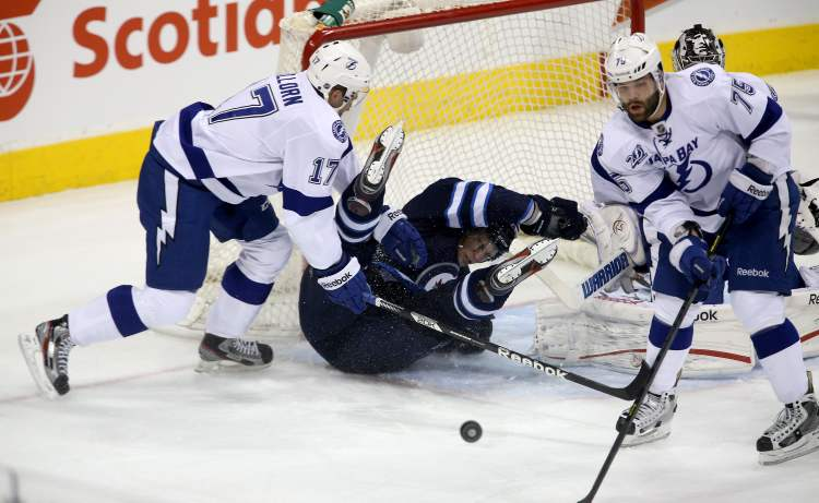 Winnipeg Jet Eric Tangradi slides into the net between Tampa Bay Lightnings' Alex Killorn (17), Radko Gudas (75) and goaltender Ben Bishop. (Trevor Hagan / THE CANADIAN PRESS)