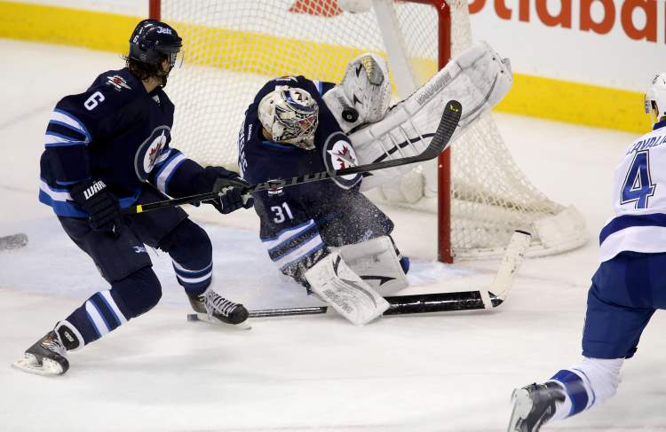 Winnipeg Jets defenceman Ron Hainsey looks on as Jets goaltender Ondrej Pavelec makes a save against Tampa Bay Lightning captain Vincent Lecavalier.