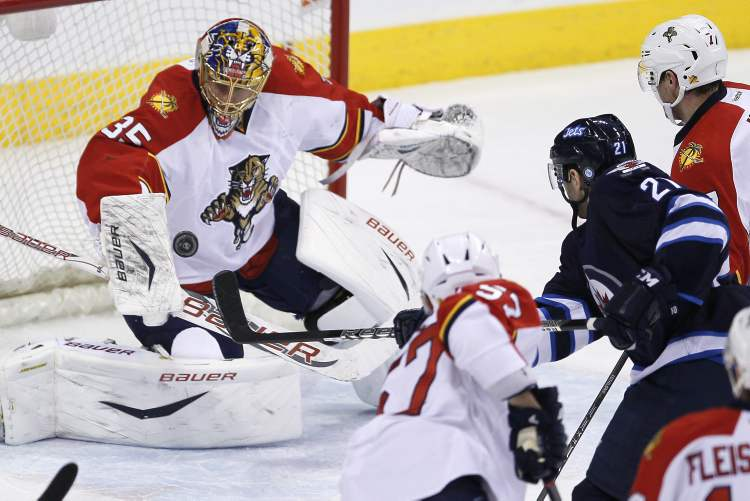 Florida Panthers goaltender Jacob Markstrom stops the shot from Winnipeg Jets' Aaron Gagnon as Panthers' Marcel Goc (57) and Dmitry Kulikov (7) look for a rebound during first-period NHL action in Winnipeg Thursday.