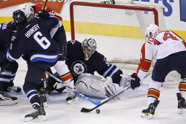Florida Panthers' Tomas Fleischmann can't get the puck past Winnipeg Jets goaltender Ondrej Pavelec as Jets Dustin Byfuglien and Ron Hainsey take control of Panther Tomas Kopecky during the third period Thursday.